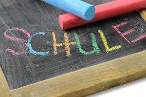 Tafel mit Kreide und bunter Aufschrift Schule