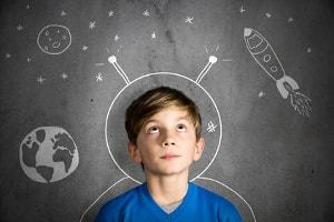 Schüler vor Tafelzeichnung mit Astronautenhelm,  Weltall und Rakete